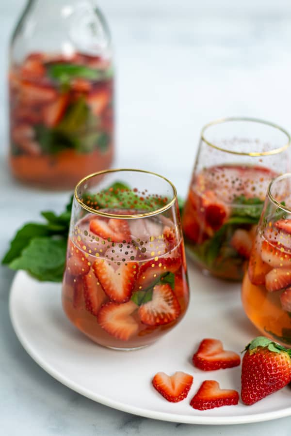 threes glasses of strawberry sangria on a plate with cut strawberries and basil