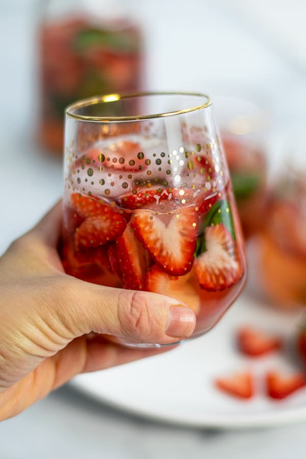 a hand holding a glass of strawberry basil sangria made with rosé wine