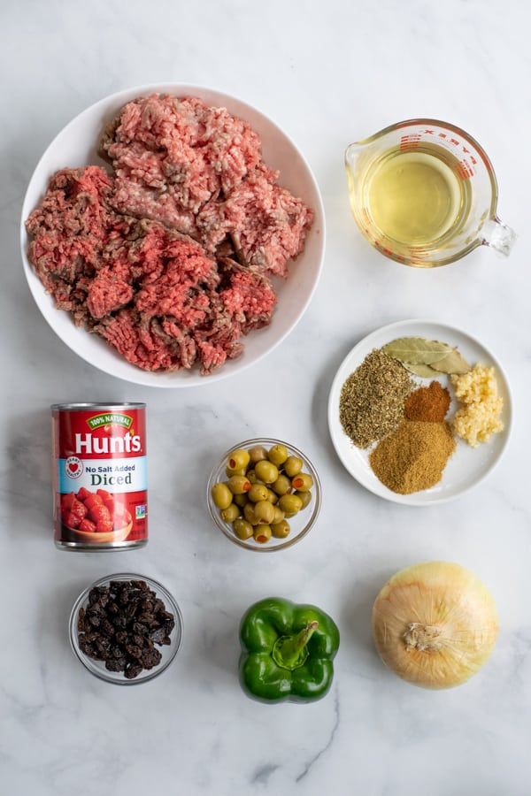 all of the ingredients needed to make picadillo laid out on a counter