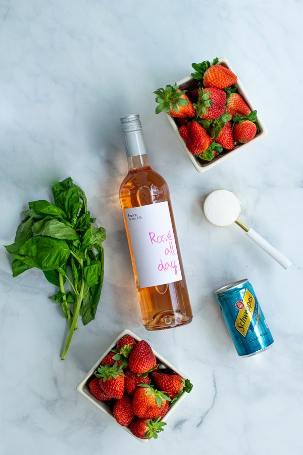 ingredients for strawberry sangria, rosé wine, strawberries, sugar, basil, and club soda
