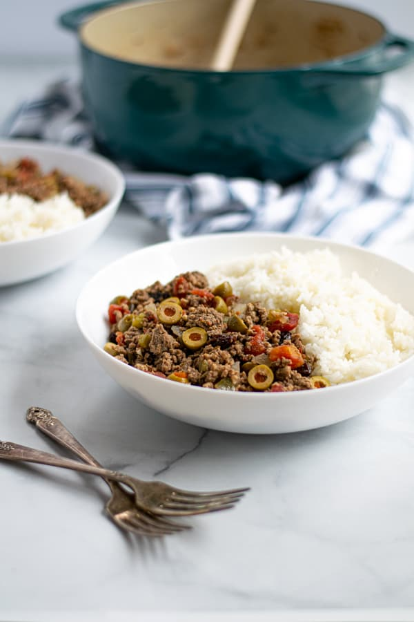 white bowl filled with rice and cuban picadillo full with tomatoes, olives, and raisins