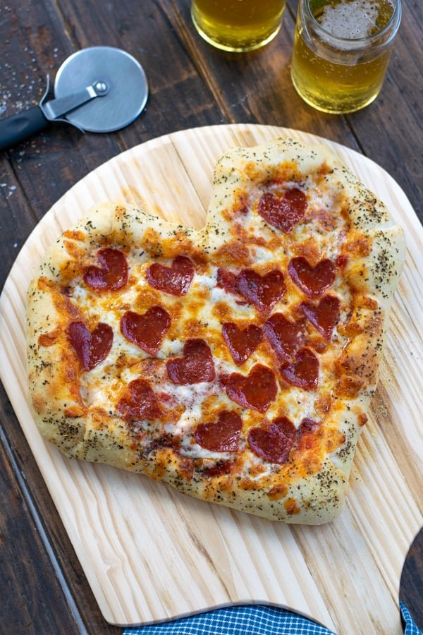 side angle of the heart shaped pizza freshly out of the oven with puffy crust and browned cheese