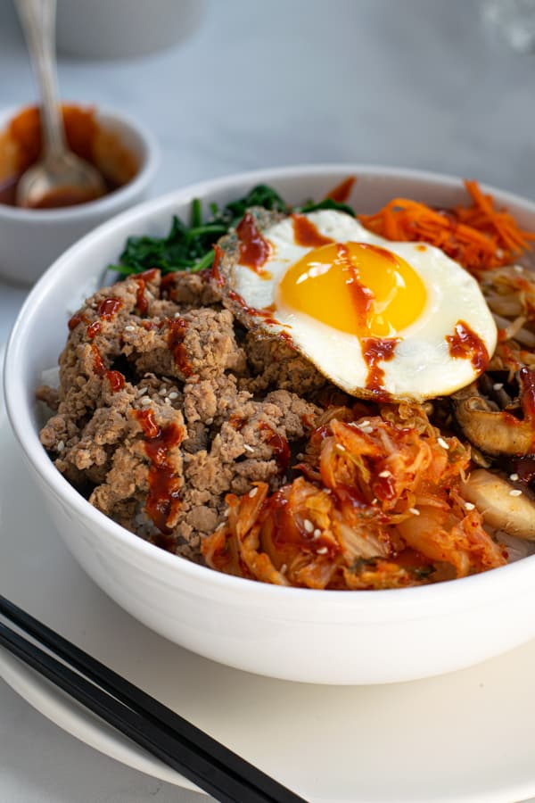 turkey bibimbap recipe in a bowl topped with an egg and drizzled with Gochujang sauce