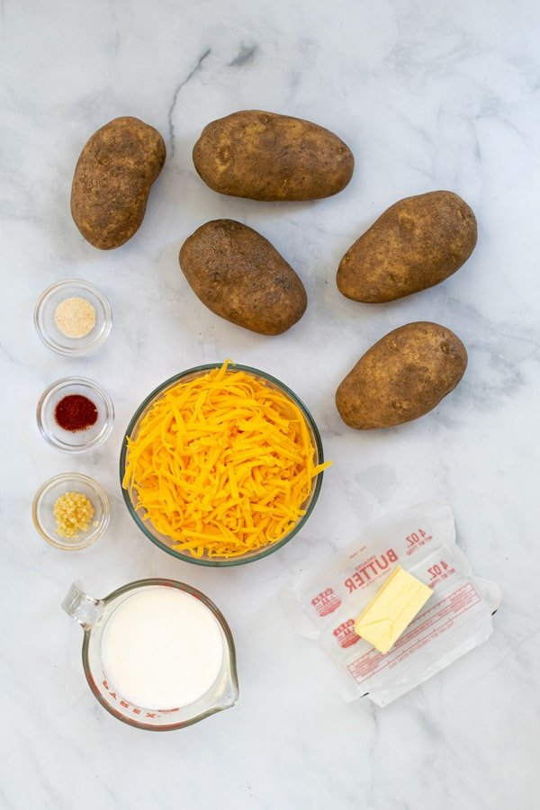 ingredients, potatoes, cheese, cream, butter, and spices to make Au Gratin Potatoes