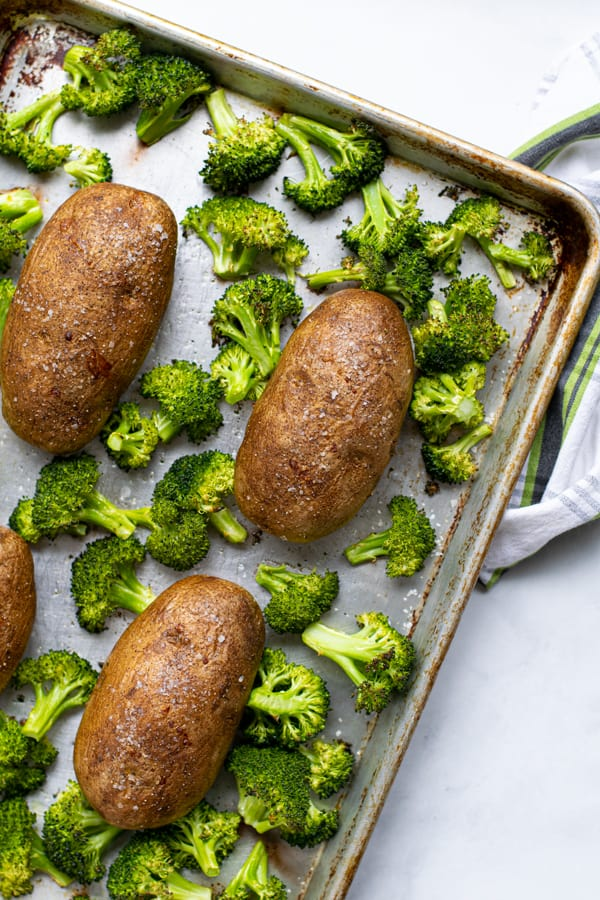 baked potatoes and roasted broccoli on a sheet pan