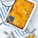 homemade au gratin potatoes in a white casserole dish with a some on a plate next to it with the title of the recipe