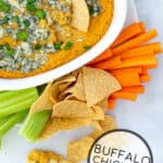 Buffalo Chickpea Dip with tortilla chips and veggie sticks for dipping