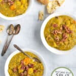 a pinterest pin with 3 bowls of split pea soup on a table with spoons and bread rolls