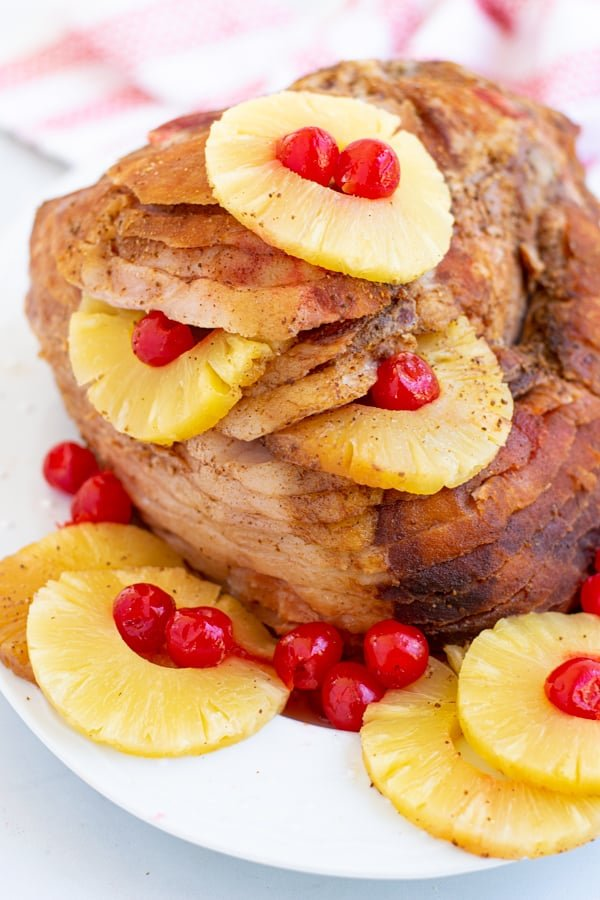 an easter ham on a white platter with pineapple rings and maraschino cherries for garnish