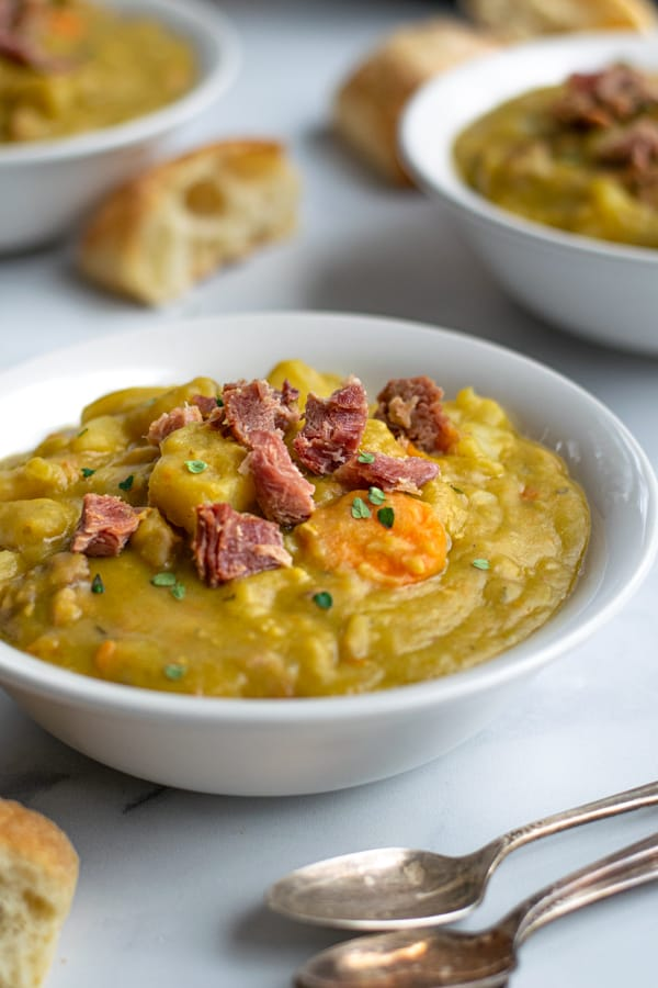 bowl of split pea soup with pieces of ham on time, sprinkled with fresh thyme