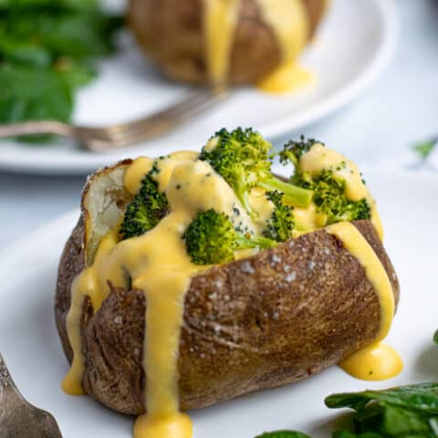 easy to make Broccoli Cheese Baked Potato on a plate with cheddar cheese sauce dripping down the side