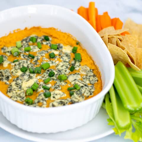 easy Buffalo Chickpea Dip in a small white baking dish with blue cheese and green onions with chips and vegetables for serving
