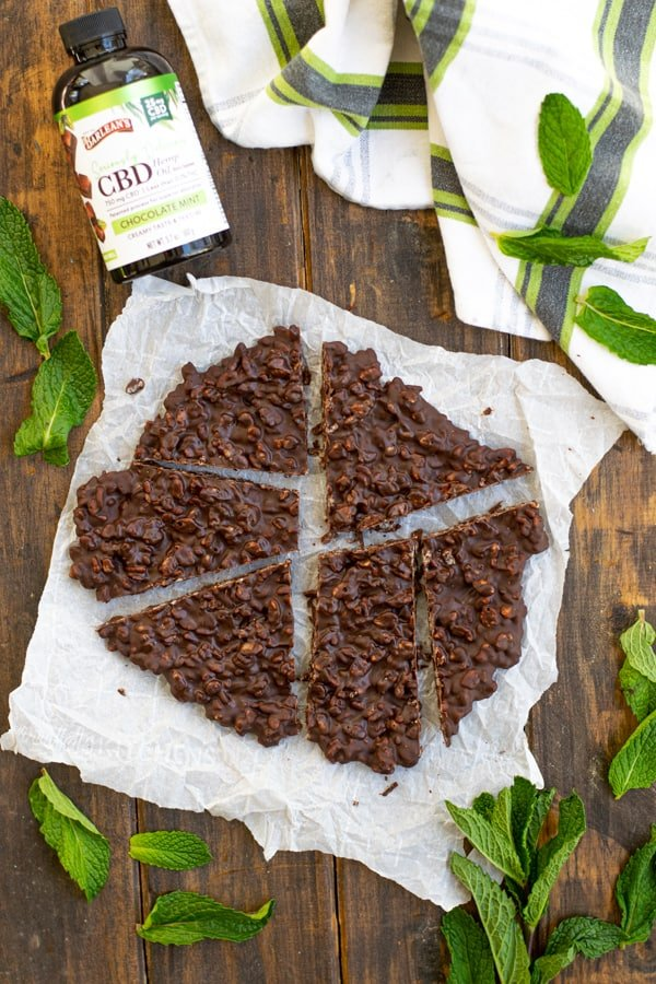 Chocolate Mint Crunch Bar cut into many pieces on a piece of parchment paper with mint leaves tossed around