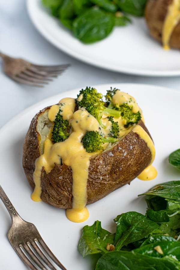 broccoli stuffed inside a baked potato topped with a creamy cheese sauce on a plate