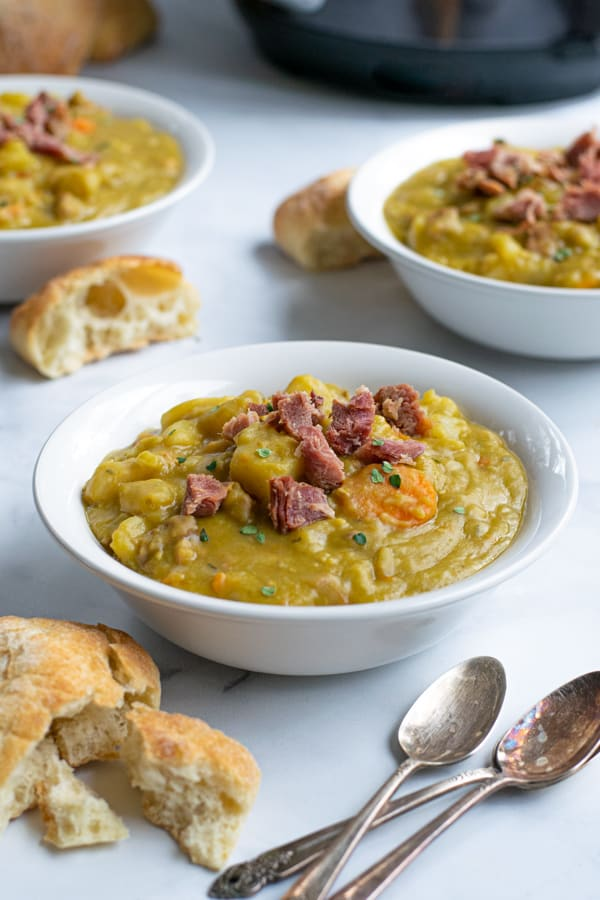 a bowl with split pea soup topped with ham and sprinkled with fresh thyme