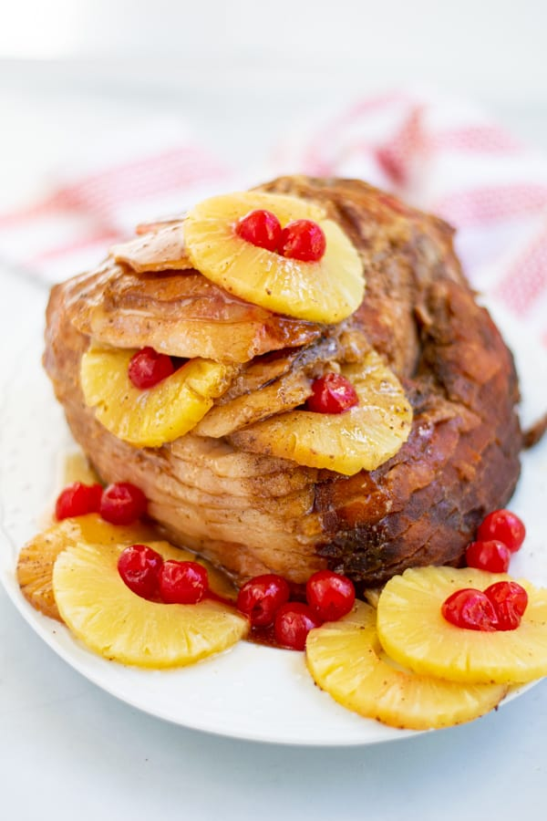 a glazed ham on a platter with pineapple slices and cherries