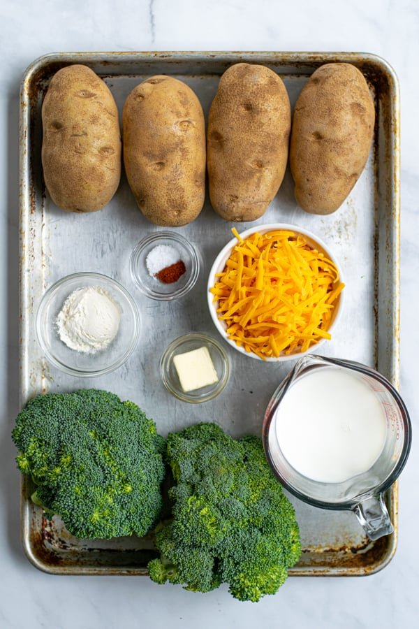 a sheet pan containing all of the ingredients needed to make broccoli cheese baked potatoes
