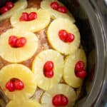 a spiral ham in the slow cooker covered by a brown sugar rub, pineapple slices, and cherries