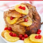 spiral ham on a platter with pineapples and cherries with a brown sugar glaze