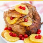 ham on a platter with pineapples and cherries with a brown sugar glaze