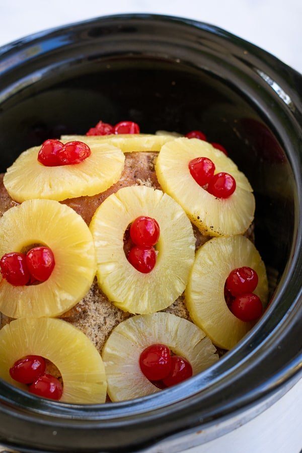 pineapple slices on a ham in a crockpot with maraschino cherries