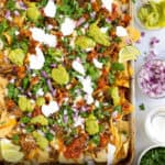 Pinterest Pin with a sheet pan of carnitas nachos with cheese and toppings