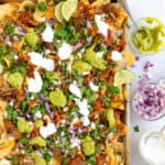Carnitas Nachos Pinterest Pin with a sheet pan of nachos with pork, cheese, and toppings
