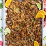 Easy crockpot carnitas on a sheet pan with lime and orange slices