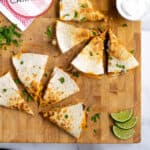 Pineterst Pin with post title showing two carnitas quesadillas on a wooden cutting board