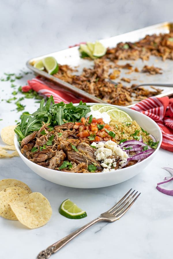 a carnitas bowl featuring a base of leftover carnitas, quinoa, and arugula with fresh topping make an excellent fast meal