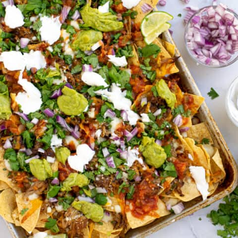 a sheet pan full of carnitas nachos topped with cilantro, red onion, guacamole, and more