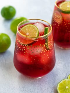 Hibiscus Iced Tea Sparkler in a glass with ice and limes