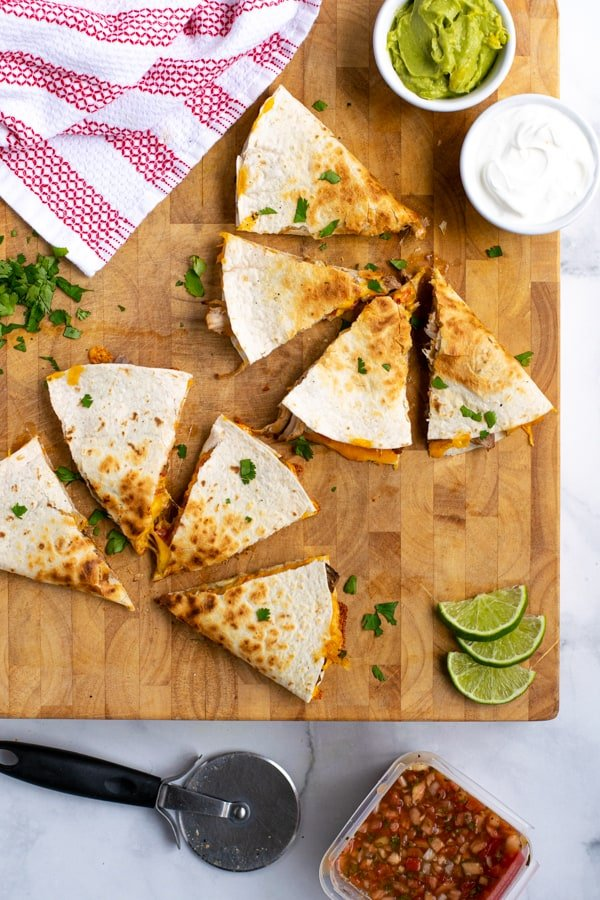 two carnitas quesadillas cut into pieces on a wooden cutting board with garnishes nearby