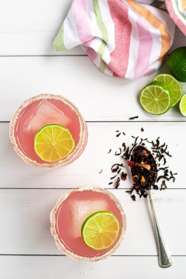 two bright pink hibiscus margaritas shot from above with a colorful towel and dried hibiscus tea