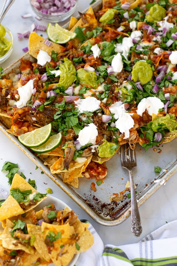 a fork on a sheet pan full of carnitas nachos pulling some off onto a plate