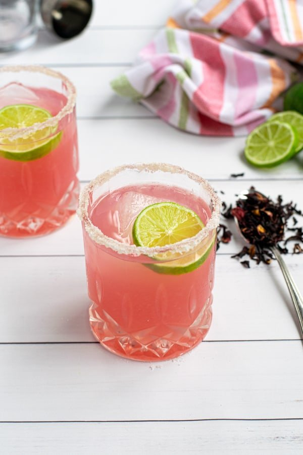 hibiscus margarita on a white table in a glass with a salted-rim and lime wheel