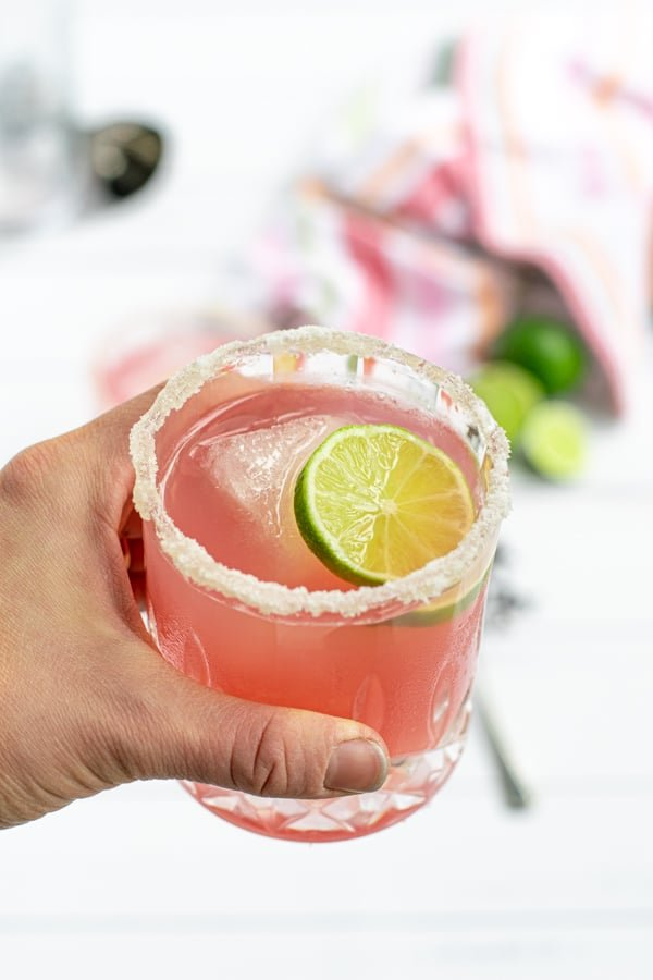 hand holding a glass of hibiscus margarita with a lime slice