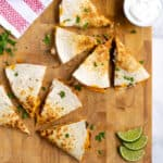 Pinterest Pin with post title showing photo two cut quesadillas on a cutting board
