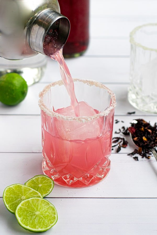 pink hibiscus margarita being poured from a cocktail shaker into a salt-rimmed glass