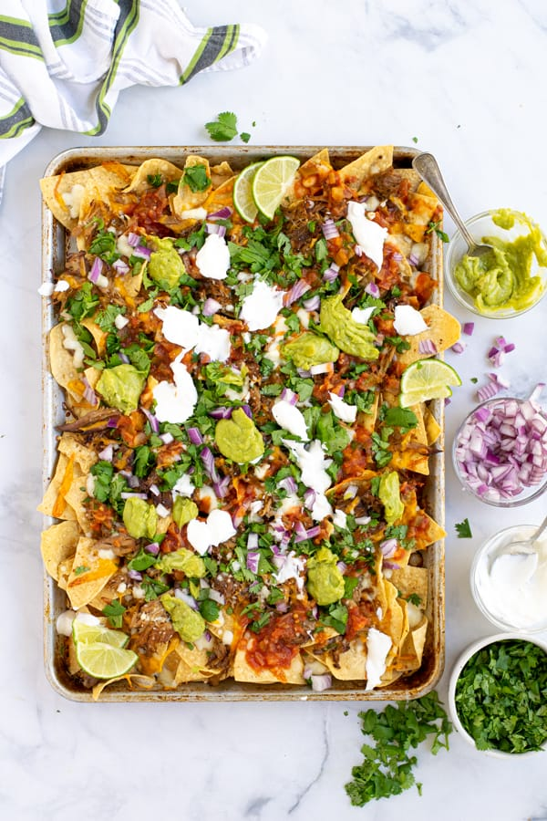 sheet pan full of nachos with carnitas, cheese, and toppings