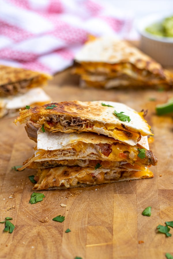 stack of 3 carnitas quesadillas on a wooden cutting board