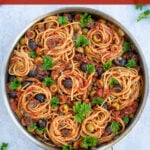 Spaghetti Puttanesca Pinterest Pin showing a large skillet full of pasta garnished with parsley