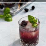 Pinterest Pin for Bourbon Blackberry Smash Cocktail showing photo of purple drink garnished with basil leaves and fresh blackberries