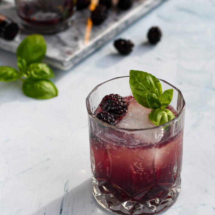 an old fashioned glass filled with a purple blackberry bourbon smash garnished with a large ice cube, blackberries, and basil