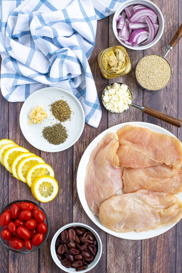 all of the ingredients you need laid out on a table to make greek chicken bake