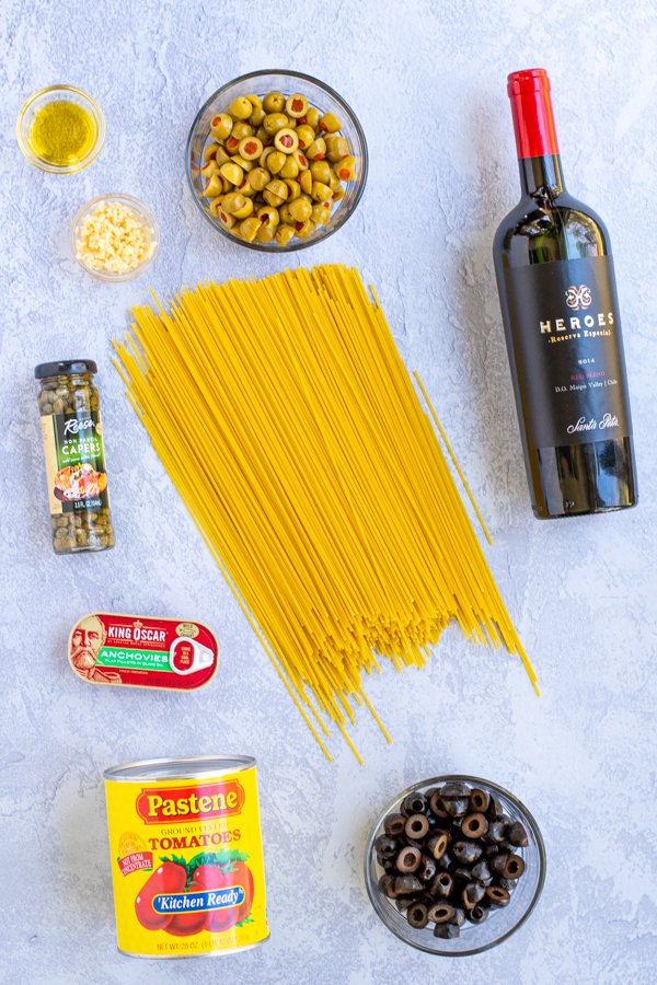 Layout of all of the ingredients needed for Spaghetti Puttanesca including wine, spaghetti, tomatoes, olives, capers, anchovies, oil, and garlic