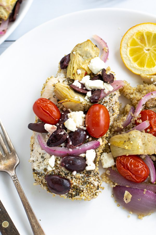 close up of a greek baked chicken breast with topping on top