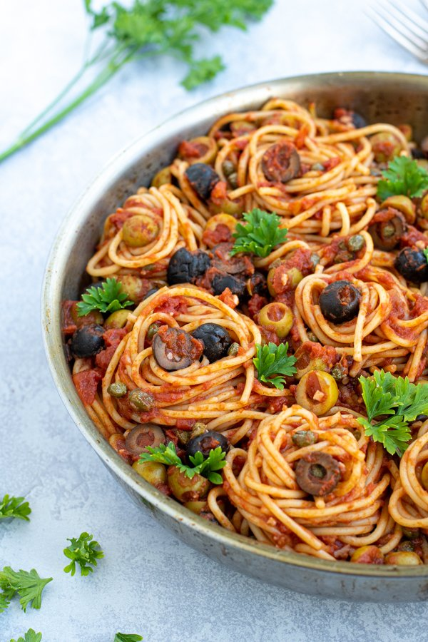 close up of pasta twirled into nests inside of a large skillet garnished by olives and parsley