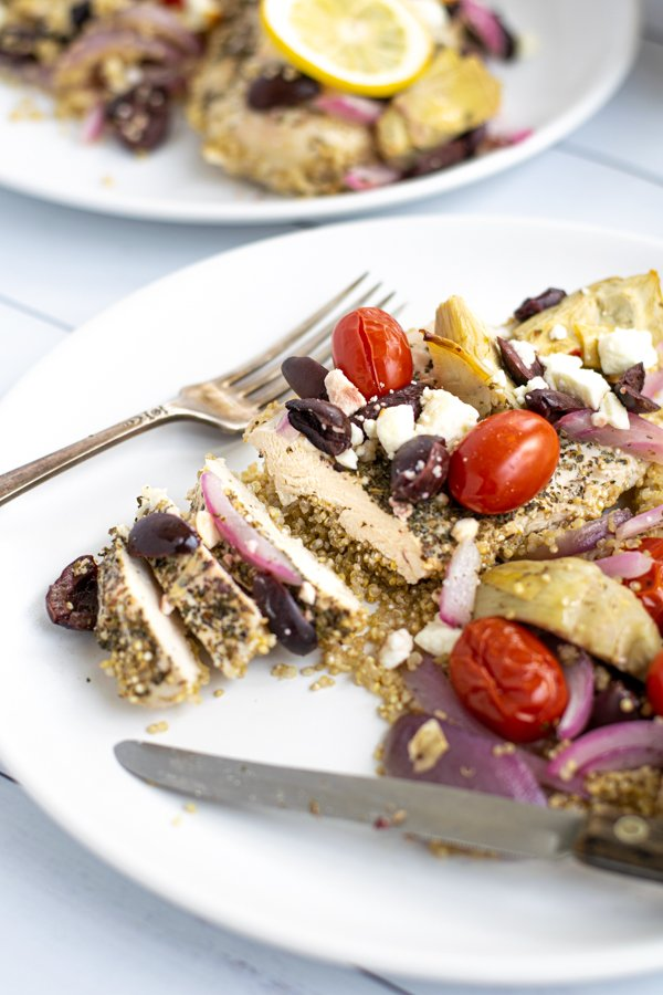 a cut chicken breast with greek toppings and quinoa on a white plate with a knife and fork