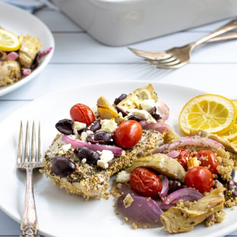 a baked greek chicken breast on a plate with greek toppings and quinoa